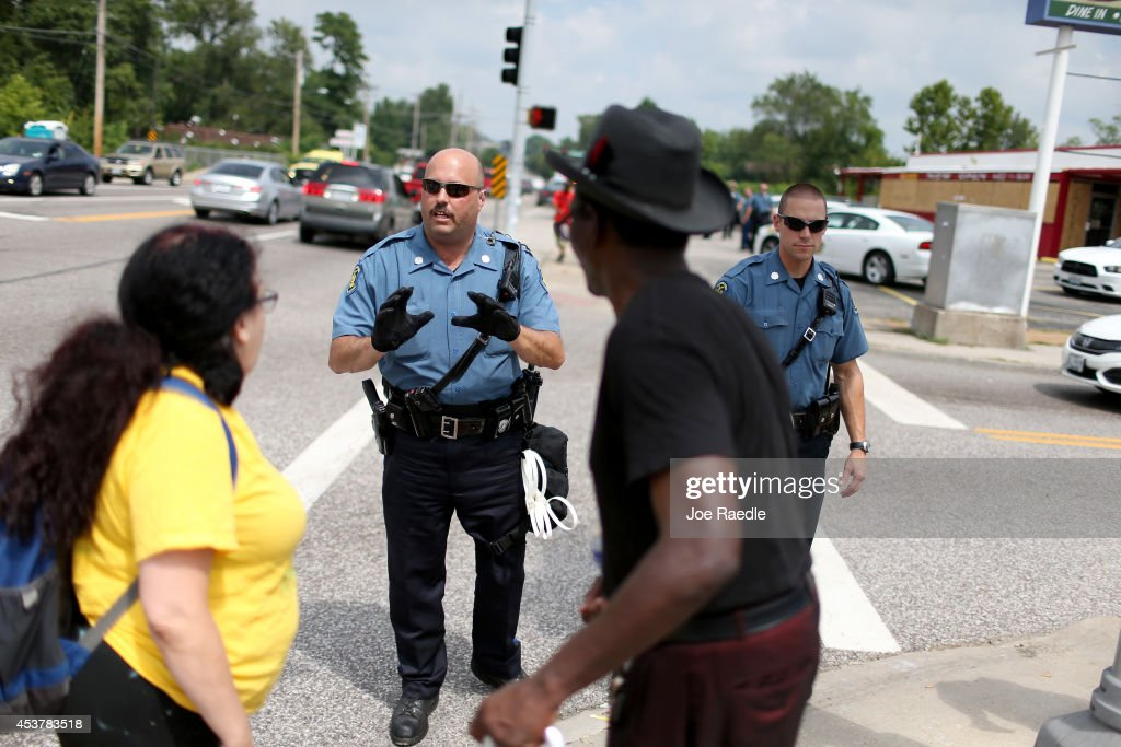 Police officers advise demonstrators protesting the shooting death of Michael Brown that they can't stop walking as they make their voices heard on August 18, 2014 in Ferguson, Missouri. Protesters have been vocal asking for justice in the shooting death of Michael Brown by a Ferguson police officer on August 9th.