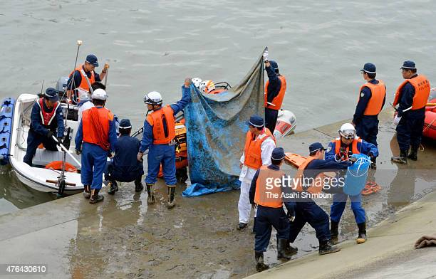Police officers and fire fighters recover a body of the missing 15yearold boy from the Aizumagawa River on June 9 2015 in Kariya Aichi Japan The boy...