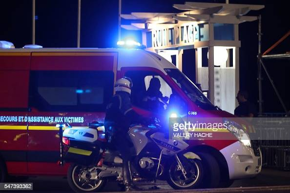 Police officers and firefighters arrive near the site of an attack on July 14 after a truck ploughed into a crowd leaving a fireworks display in the...