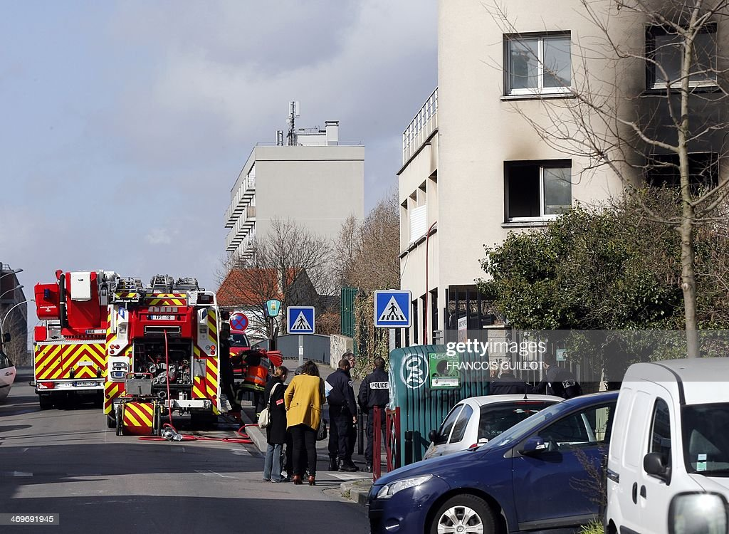 Police officers and firefighters gather near a building containing offices and apartments in Montreuil, in the eastern suburbs of Paris, after a fire broke out early on February 16, 2014. An 18-year-old man died in the fire, another person was seriously injured and four others sustained minor injuries, according to firefighters at the scene.