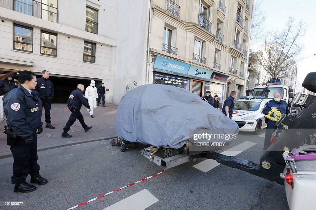 Police officers and forensic experts move a car after searching for evidence on February 17, 2013 in Montrouge, a southern Paris suburb, after a 20-year old woman was seriously wounded in her vehicle by gun shots.