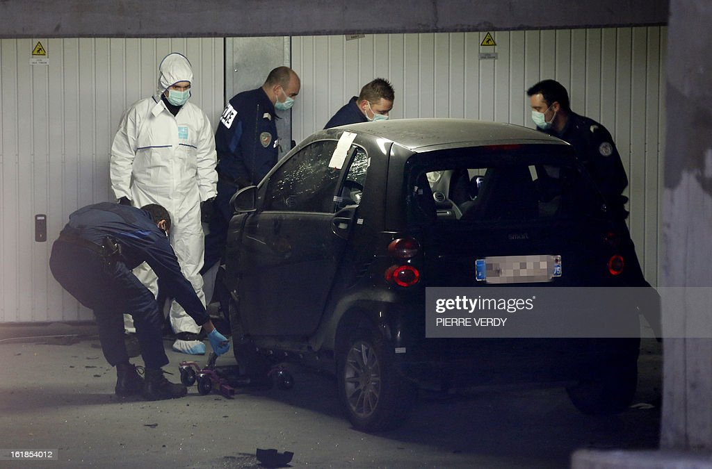 Police officers and forensic experts search for evidence around a car on February 17, 2013 in Montrouge, a southern Paris suburb, after a 20-year old woman was seriously wounded in her vehicle by gun shots. AFP PHOTO / PIERRE VERDY