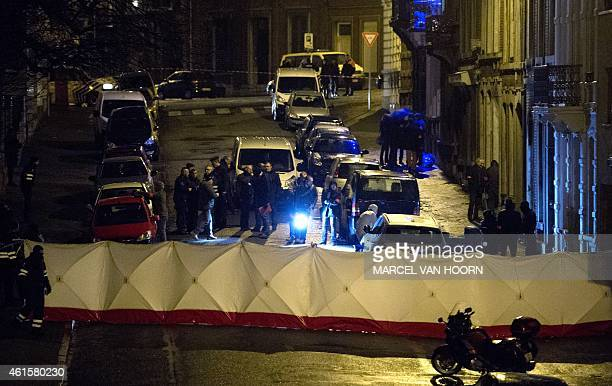 Police officers and forensic police work in a cordoned off section of Colline street in Verviers eastern Belgium on January 15 after two suspects...