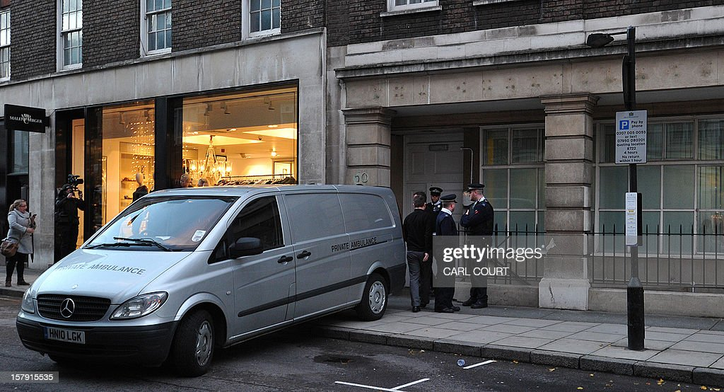Police officers and hospital staff stand by the rear of a coroners van after a body was loaded from a nurses accommodation block near the King Edward VII hospital in central London on December 7, 2012 where nurse Jacintha Saldanha was found dead. A nurse at the hospital which treated Prince William's pregnant wife Catherine, Duchess of Cambridge, was found dead on December 7, days after being duped by a hoax call from an Australian radio station, the hospital said. Police said they were treating the death, which happened at a property near the hospital, as unexplained. AFP PHOTO / CARL COURT