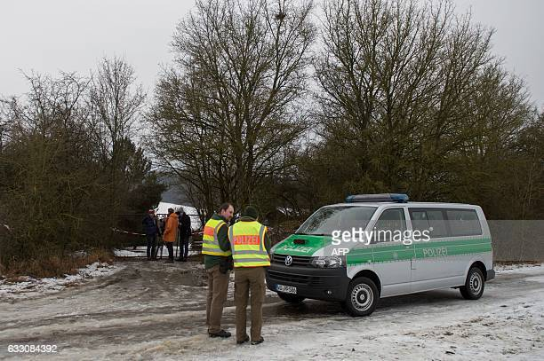 Police officers and journalists stand in front of the fence blocking the access to the private property where six teenagers were found dead in...