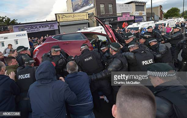 Police officers and local nationalist residents attend to Phoebe Clawson trapped underneath a car allegedly driven by a loyalist as it reversed at...