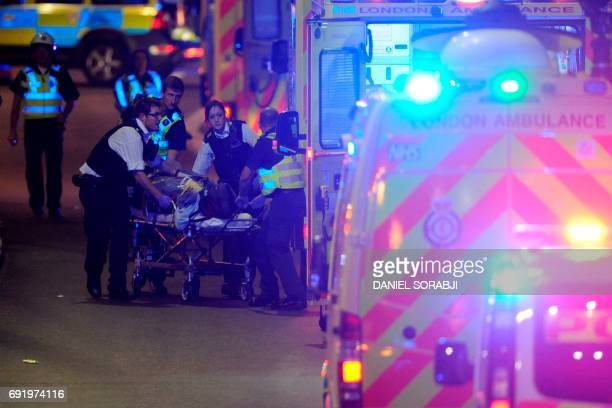 Police officers and members of the emergency services attend to a person injured in an apparent terror attack on London Bridge in central London on...