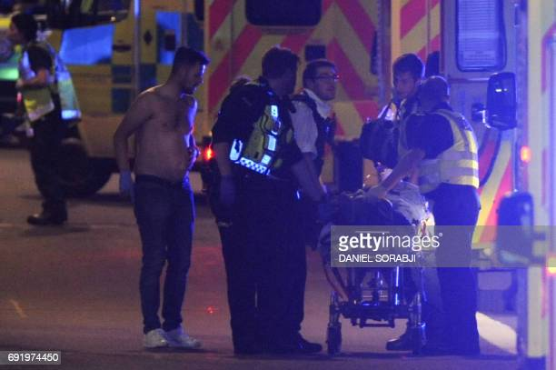 Police officers and members of the emergency services attend to a person injured at the scene of an apparent terror attack on London Bridge in...