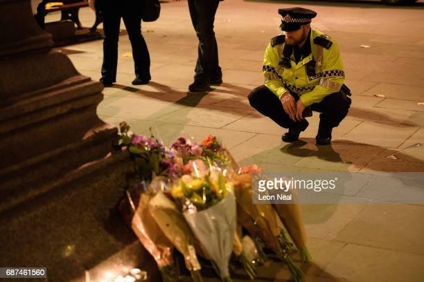 Police officers and members of the public look at some of the floral tributes following an evening vigil outside the Town Hall on May 23 2017 in...