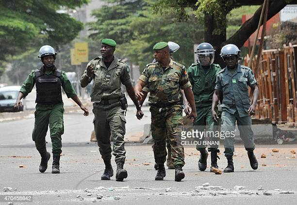 Police officers and militaries walk in a street during an antigovernment protest in Conakry on April 20 2015 Guinean police opened fire on...