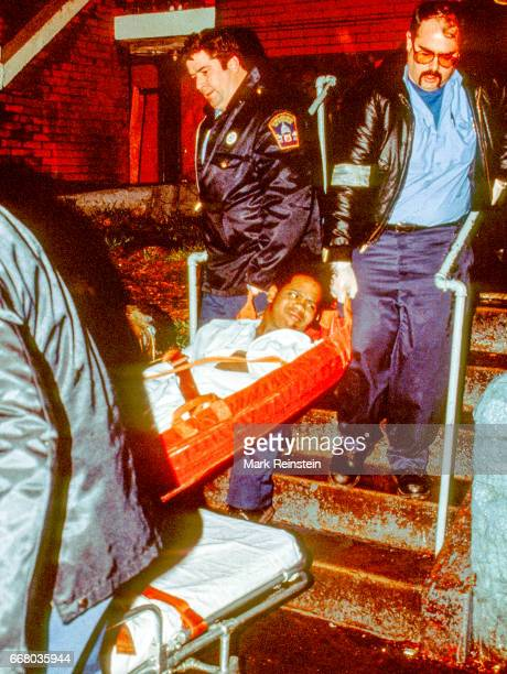 Police officers and paramedics carry a shooting victim on a stretcher out of an apartment building Washington DC 1989