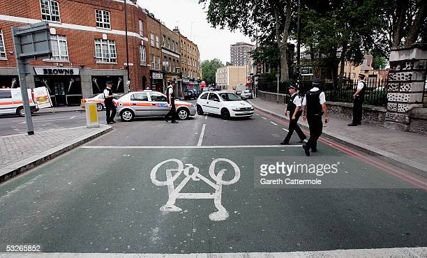 Police officers and police car vehicles wait on the closed Hackney Road in Bethnal Green on July 21 2005 in London England The windows were blown out...