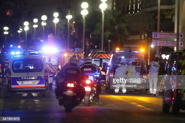 Police officers and rescue workers arrive at the scene of an attack on July 14 after a truck ploughed into a crowd leaving a fireworks display in the...