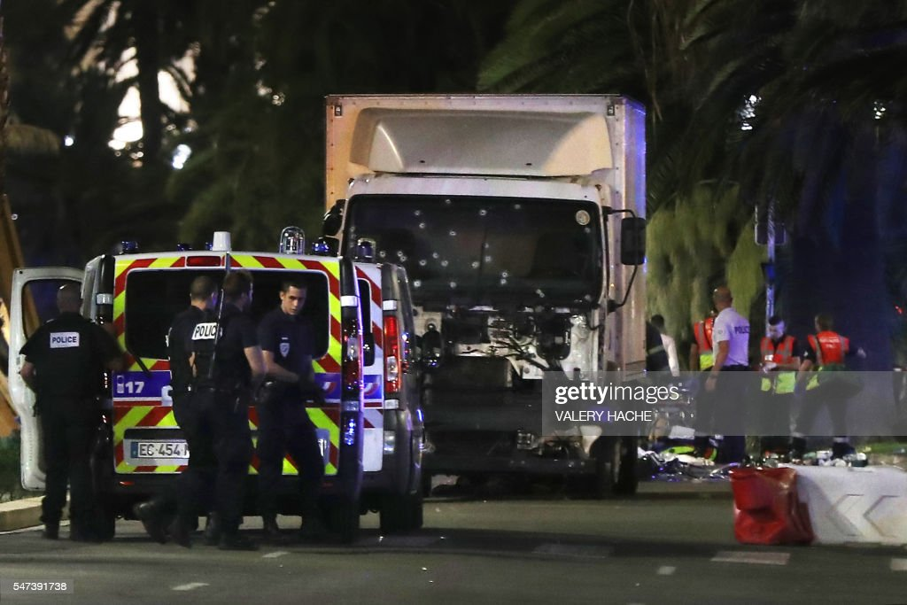 Police officers and rescue workers stand near a van that ploughed into a crowd leaving a fireworks display in the French Riviera town of Nice on July...