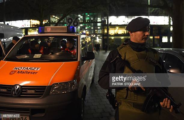 Police officers and rescuers stand at the entrance of the stadium as supporters leave the HDI Arena after the friendly football match Germany vs the...