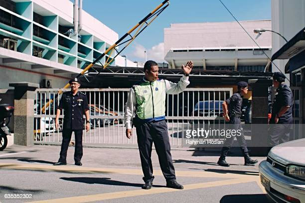 Police officers and security guard the entrance of the forensic department of Kuala Lumpur General Hospital where the body Jongnam is believed to be...