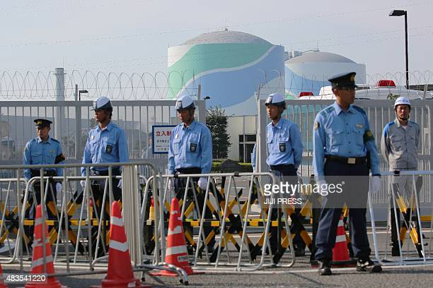 Police officers and security personnel stand in front of the gate of the Kyushu Electric Power Sendai nuclear power plant as antinuclear protesters...
