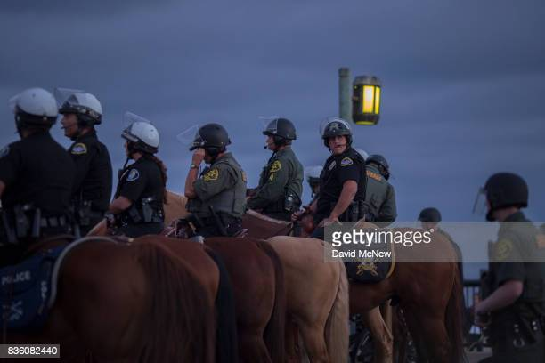 Police officers and Sheriff deputies on horseback form a line to keep demonstrators and counter demonstrators apart at an 'America First'...