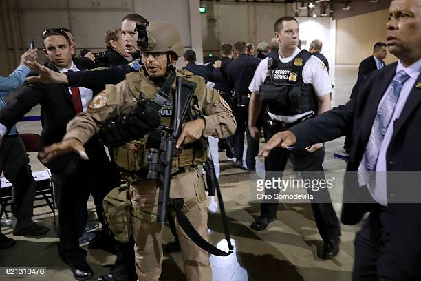 Police officers and US Secret Service rush a man in handcuffs out of a campaign rally for Republican presidential nominee Donald Trump at the...