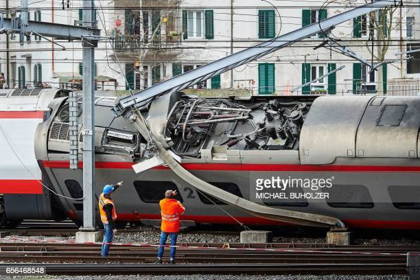 Police officers and workers inspect the site of a train crash at the train station of Lucerne where a Eurocity train of Trenitalia derailed on March...