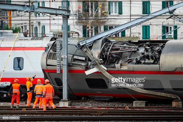 TOPSHOT Police officers and workers inspect the site of a train crash at the train station of Lucerne where a Eurocity train of Trenitalia derailed...