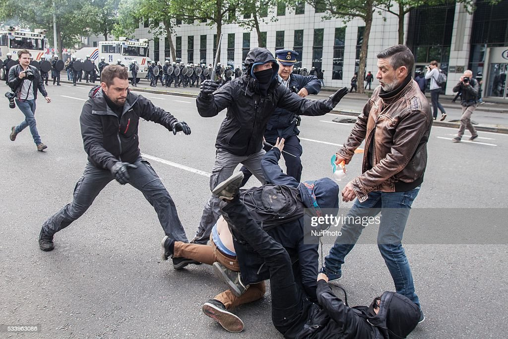 Police officers are arresting a protester who was throwing rocks at the police. An anti-government demonstration ended up in a riot, in which one officer got injured and several protesters were arrested in Brussels on May 24, 2016.