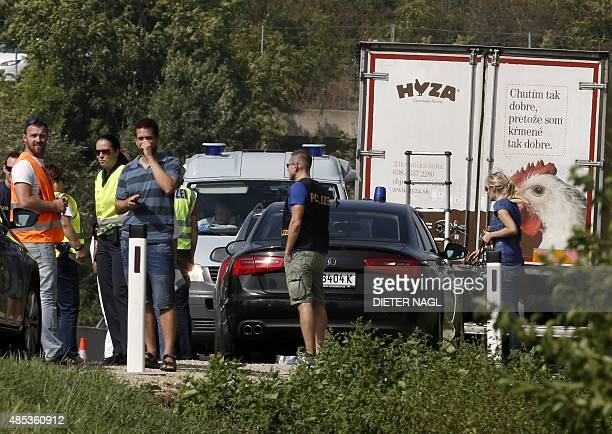 Police officers are seen around a refrigerated truck parked along a highway near Neusiedl am See Austria on August 27 2015 The bodies of between 20...