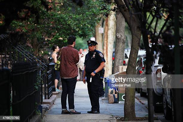 Police officers are seen by a crime scene where three people were shot on June 10 2015 in the Gowanus area of the Brooklyn Borough of New York City...