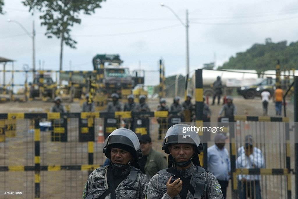 Police officers are seen during a demonstration against Norte Energia - the company responsible for the construction of Belo Monte hydroelectric power plant - demanding compensation for the loss of income from the flooding of the Xingu river near Altamira, in the northern state of Para, Brazil, on March 18, 2014. The dam will be the largest hydroelectric power plant in Brazil and provide 11% of the nation's electricity. Norte Energia says about 502km2 will be flooded and 117 social, economic and environmental projects are underway for the millions affected in the region.