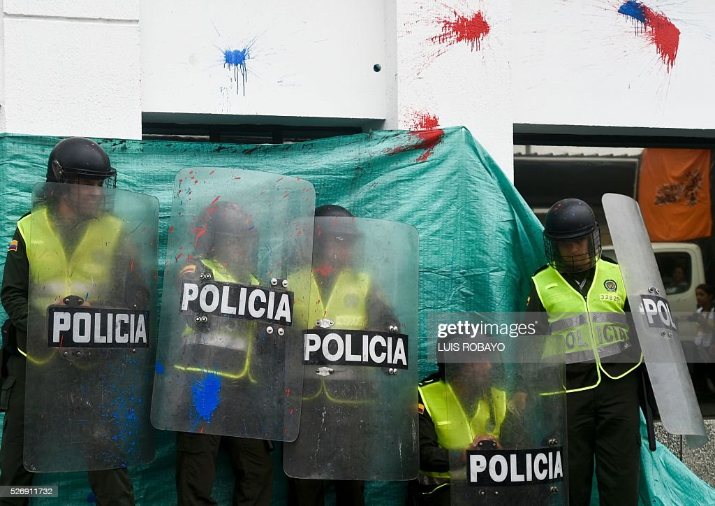 Police officers are targeted with paintballs by people marching during a demonstration to mark International Workers' Day in Cali, Colombia, on May 1, 2016. / AFP / LUIS