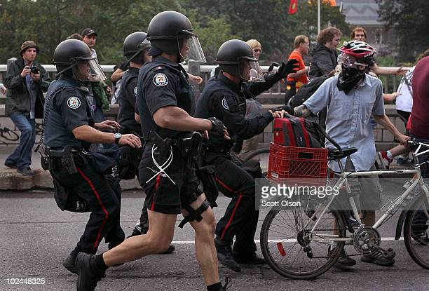 Police officers arrest a cyclist during protest against the G8/G20 summits in Queen's Park June 26 2010 in Toronto Canada Earlier in the day store...