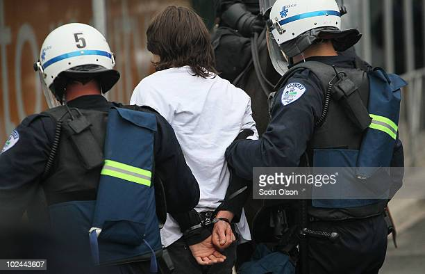 Police officers arrest a demonstrator who was protesting the G8/G20 summits on June 26 2010 in Toronto Ontario Canada Store windows were smashed and...