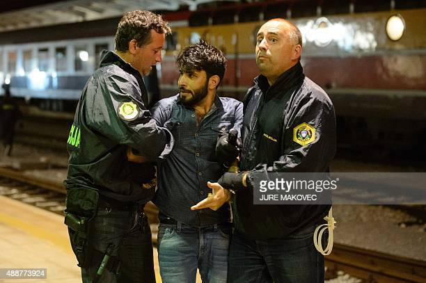 Police officers arrest a migrant who tried to board a train at the railway station near the SlovenianCroatian border in Dobova Brezice on September...