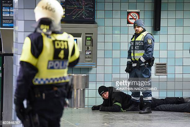 Police officers arrest a protester of the neonazi Nordic Resistance Movement in central Stockholm on November 12 2016 after a protest against...