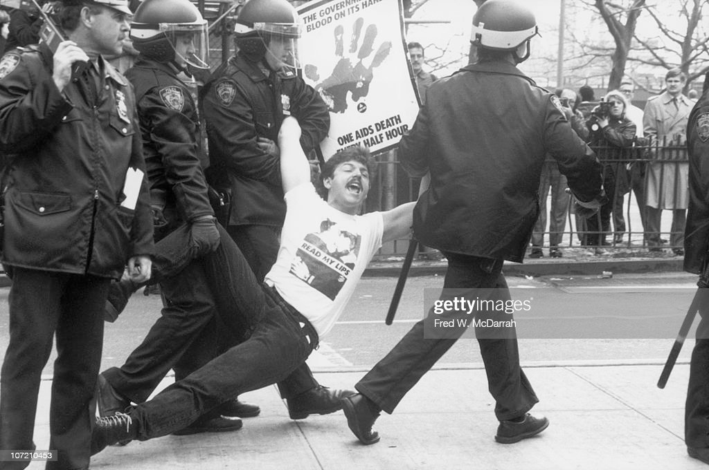 Police officers arrest and drag away a demontrator at an ACT UP protest near City Hall New York New York Mzrch 28 1989 The demonstrator wears a...