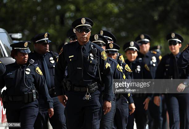 Police officers arrive at a funeral service for slain Dallas Area Rapid Transit police officer Brent Thompson at the Potter House Church on July 13...