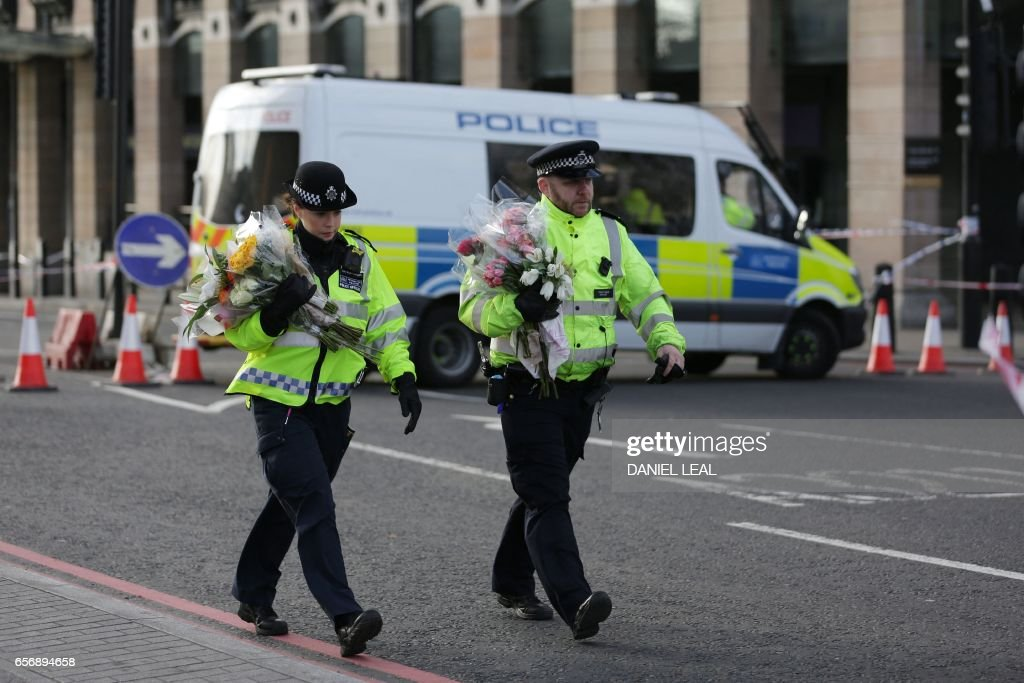 TOPSHOT - Police officers arrive carrying bunches of flowers to lay in honour of the victims of the March 22 terror attack at the end of Westminster Bridge by the Houses of Parliament in central London on March 23, 2017 after the bridge reopened. Britain's parliament reopened on Thursday with a minute's silence in a gesture of defiance a day after an attacker sowed terror in the heart of Westminster, killing three people before being shot dead. Sombre-looking lawmakers in a packed House of Commons chamber bowed their heads and police officers also marked the silence standing outside the headquarters of London's Metropolitan Police nearby. OLIVAS