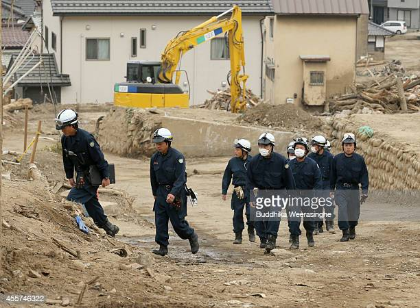 Police officers arrive to observe a moment of silence for the victims of the massive landslide at Asamiminami one month after the landslides on...