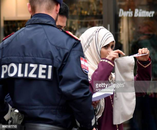 Police officers ask a woman to unveil her face in Zell am See Austria on October 1 2017 Austria's ban on fullface Islamic veils comes into force...