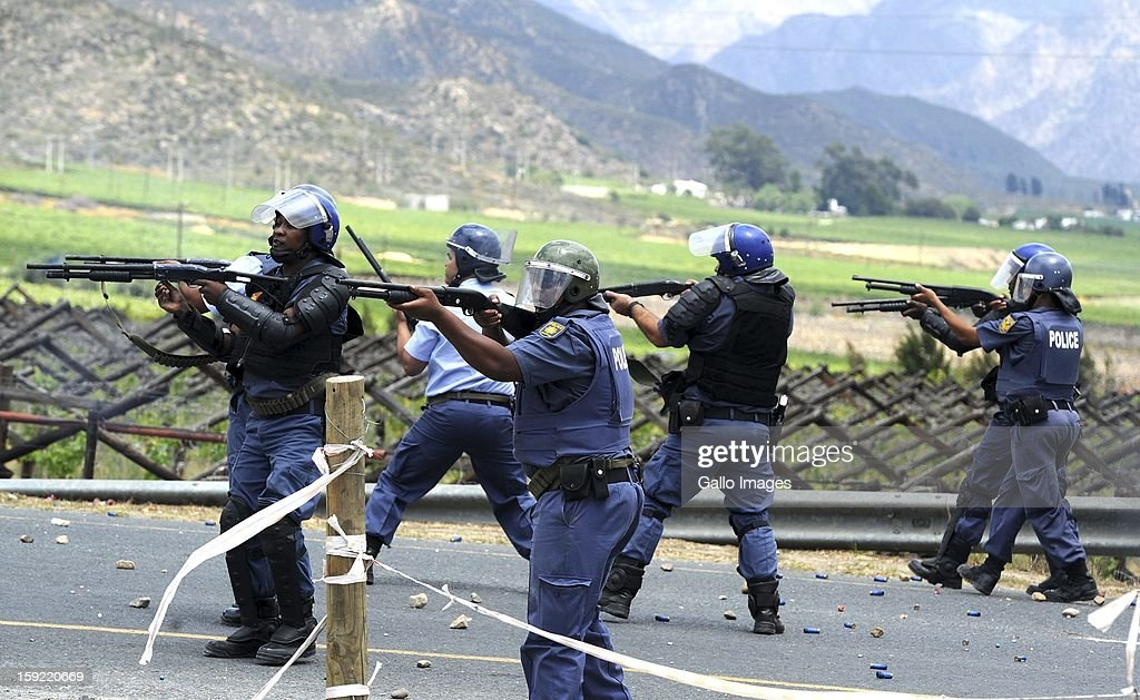 Police officers at the N1 De Doorns protest on January 9, 2013, in Cape Town, South Africa. Protesting farm workers turned violent when theu shut down the N1 by lighting tires on fire and placing large rocks on the road.