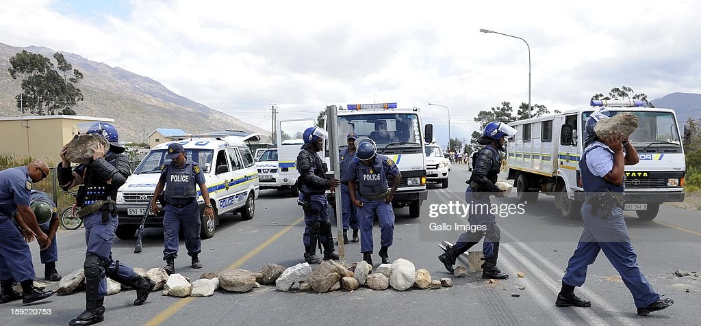 Police officers at the N1 De Doorns protest on January 9, 2013, in Cape Town, South Africa. The farm workers shut down the N1 by lighting tires on fire and placing large rocks on the road.