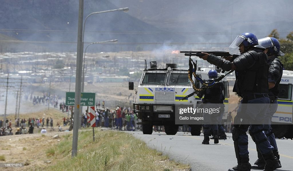 Police officers at the N1 highway De Doorns on January 9, 2013, in Cape Town, South Africa. Protesting farm workers shut down the N1 by lighting tires on fire and placing large rocks on the road.
