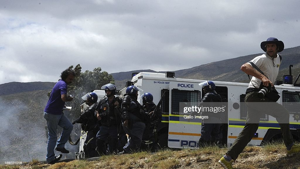 Police officers at the N1 highway De Doorns protest on January 9, 2013, in Cape Town, South Africa. The farm workers shut down the N1 by lighting tires on fire and placing large rocks on the road.
