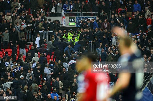 Police officers attempt to stop Millwall supporters fighting amongst themselves during the FA Cup with Budweiser Semi Final match between Millwall...
