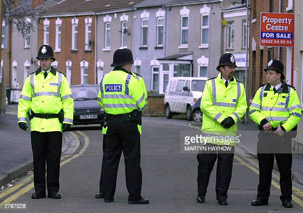 Police officers block off St James Street in Gloucester 28 November 2003 after explosive material was found at No 44 yesterday evening Police...