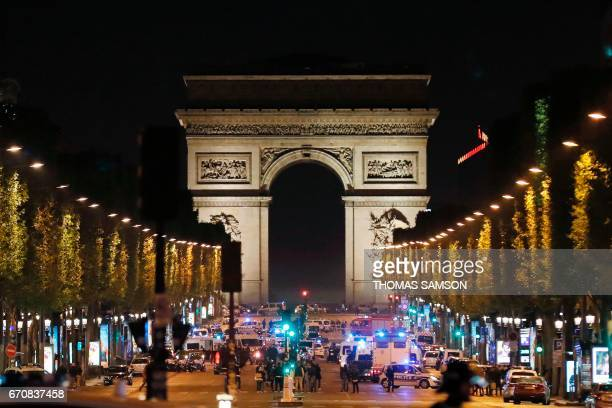 TOPSHOT Police officers block the access to the Champs Elysees in Paris near the Arc de Triomphe after a shooting on April 20 2017 One police officer...