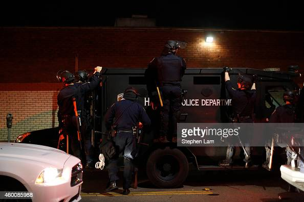 Police officers board an armored vehicle on the fourth night of demonstrations over recent grand jury decisions in policeinvolved deaths on December...