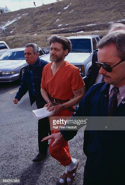 Police officers bring Theodore Kaczynski aka the Unabomber to court for arraignment Kaczynski later pled guilty to the mail bomb attacks that killed...