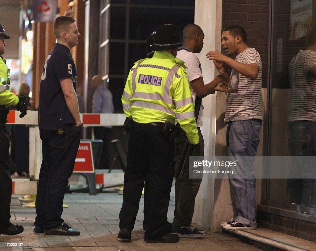 Police officers calm down boisterous behaviour as revellers walk and gather between the various pubs and clubs in Broad Street the heartland of...