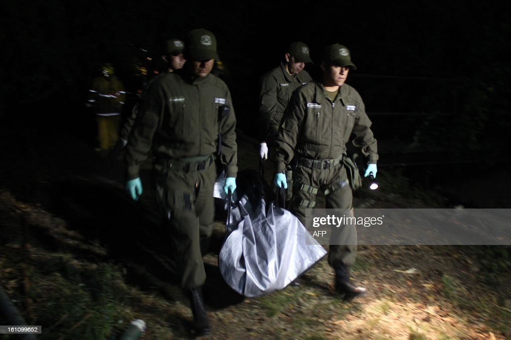 Police officers carry a corpse from an accident site after a bus driver apparently lost control in Tome, in Biobio province, some 500 km south of Santiago, on February 9,2013. At least 15 people were killed and 19 others were injured when the bus full of passengers fell into a ravine in central Chile, a local official said. AFP PHOTO/GABRIELLE RAMÍREZ